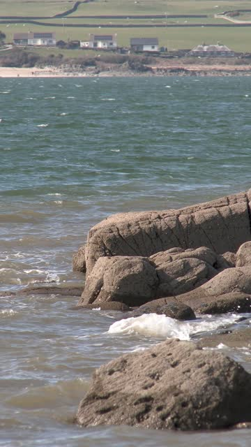 gentle waves on rocks on scottish shoreline - general view stock videos & royalty-free footage