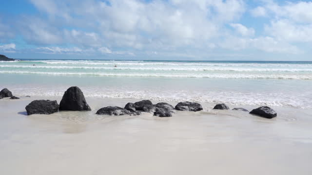 gentle waves roll into calm white sandy beach with black rocks on sunny day - galapagos islands, ecuador - south pacific ocean stock videos & royalty-free footage