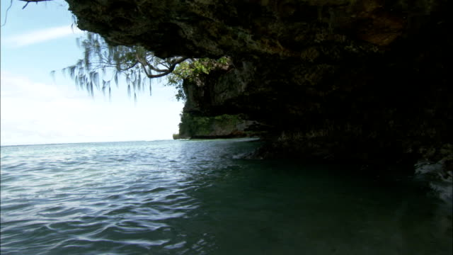 Gentle waves wash against the underside of an eroded rock island. Available in HD.