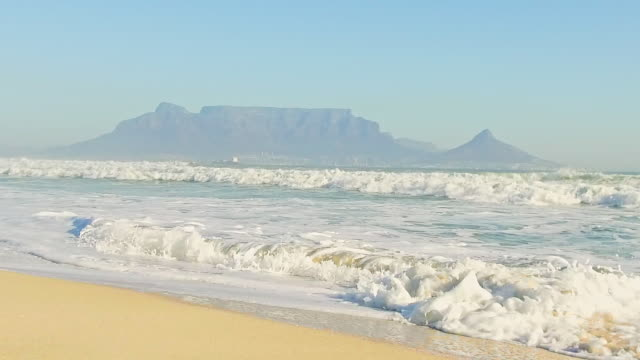 gentle waves with table mountain in the background - ライオンズヘッド点の映像素材/bロール