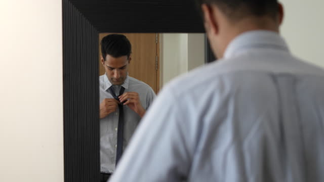 vídeos de stock e filmes b-roll de gentleman getting ready and adjusting his tie for finals checks as he prepares to go to his office - camisa e gravata
