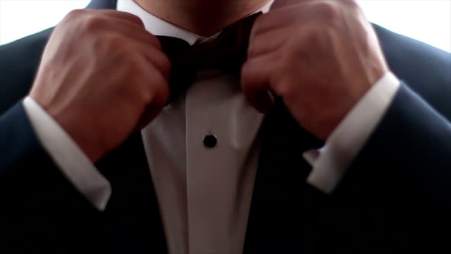 gentleman straightens his bowtie - formal stock videos and b-roll footage