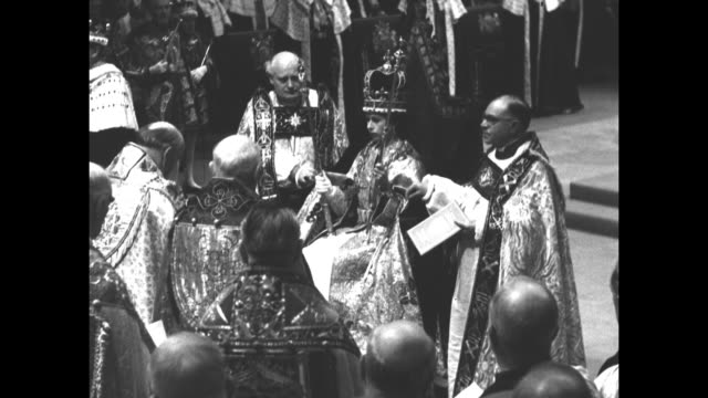 geoffrey fisher, archbishop of canterbury, places st. edward's crown on queen elizabeth ii's head as she sits in king edward's chair during her... - エリザベス・ボーズ=ライアン点の映像素材/bロール