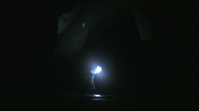 a geologist carries a flashlight as he walks through a cave. - flashlight stock videos & royalty-free footage