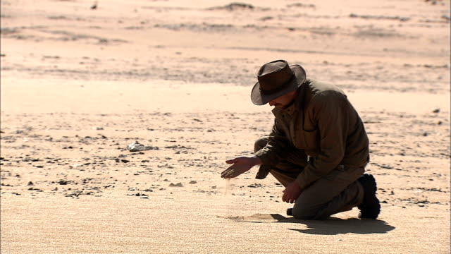 a geologist examines the texture of desert sands. - geologist stock videos & royalty-free footage