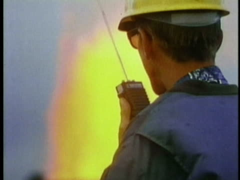 1970 ms geologist in hardhat talking on walkie-talkie with spouting lava fountain in background / kilauea volcano, hawaii / audio - geologist stock videos & royalty-free footage