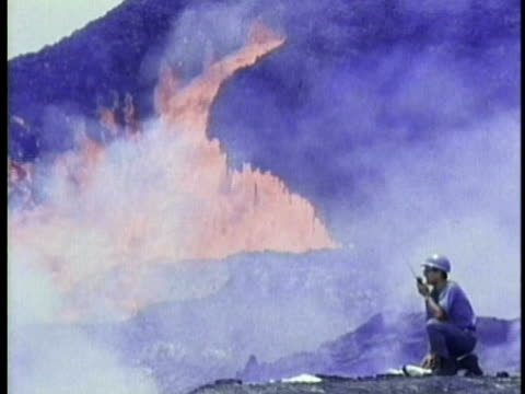 1970 ws geologist on walkie-talkie with flowing red-hot lava flowing in background / kilauea volcano, hawaii / audio - geologist stock videos & royalty-free footage