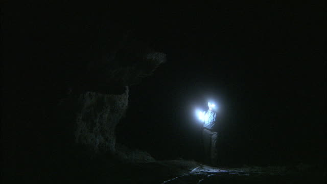 a geologist shines his lights as he walks through a cave. - geologist stock videos & royalty-free footage