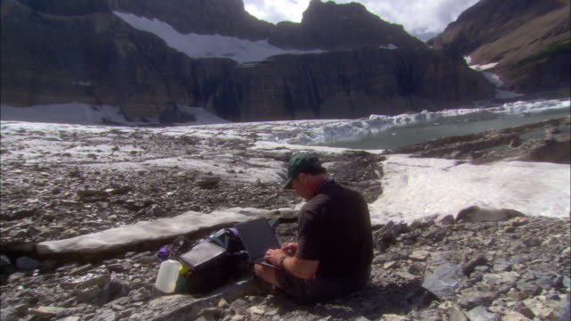 a geologist sits at the base of glaciers and enters data on his laptop in glacier national park, montana. - geologist stock videos & royalty-free footage