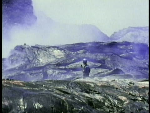 1970 ms pan geologist surveying volcanic landscape with red-hot lava in background / kilauea volcano, hawaii / audio - geologist stock videos & royalty-free footage