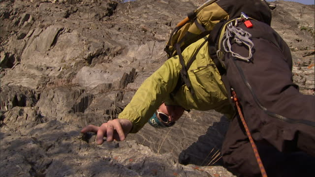 a geologist uses a hammer to flake rocks as he climbs a rugged slope. - geologist stock videos & royalty-free footage