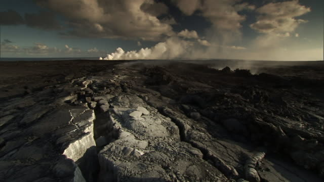 a geologist walks across a lava field and drops a wired device into a crevice. - geologist stock videos & royalty-free footage