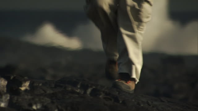 a geologist walks across a lava field and inserts a wire into a a crevice. - geologist stock videos & royalty-free footage