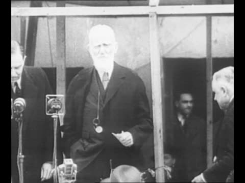 george bernard shaw at bank of microphones at event / shaw with journalists in 1933 / shaw speaks while on board the ss arandora star in 1936 / from... - ジョージ バーナード ショー点の映像素材/bロール