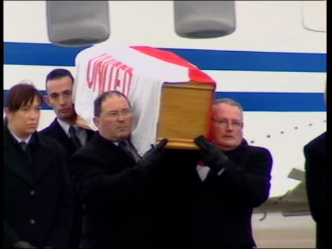 coffin flown home to belfast; bbc pool northern ireland: belfast: raf aldergrove: ext ** bagpipes playing in b/g ** coffin , draped in manchester... - bbc点の映像素材/bロール