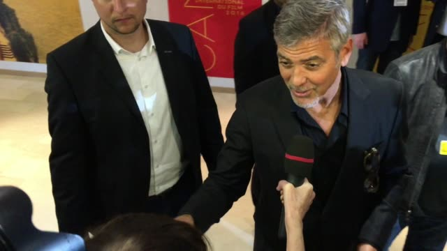 George Clooney signs autographs and chats to fans at Palais des Festivals on May 12 2016 in Cannes France