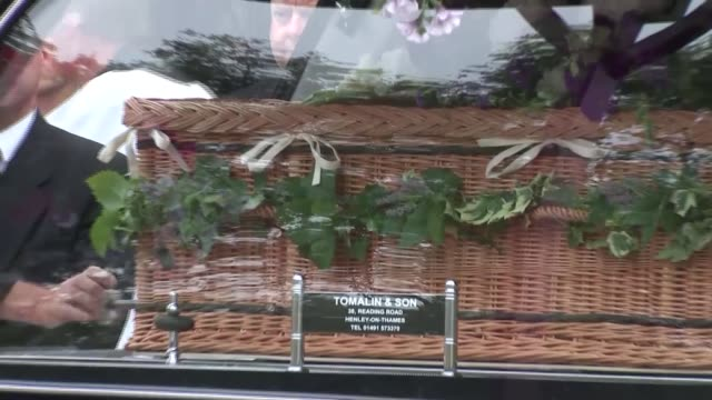 George Cole funeral Hearse along at crematorium with wicker coffin in back [Music playing] / Mourners with clergyman Coffin removed from back of...