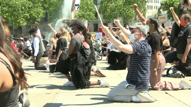 protesters march in london, berlin and copenhagen to show solidarity; england: london: trafalgar square: ext protesters kneeling and holding up fists... - ひざまずく点の映像素材/bロール