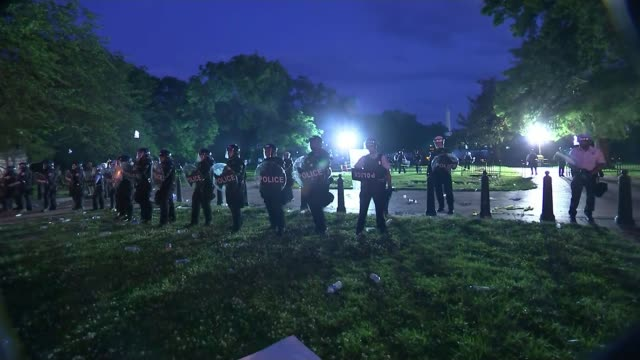 protests continue and donald trump calls for national guard; usa: washington dc: ext / night protesters standing in front of police line, one man... - ひざまずく点の映像素材/bロール