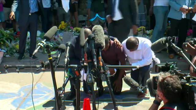 vídeos de stock, filmes e b-roll de george floyd's family pay their respects at memorial to him at place in minneapolis where he died when a police officer knelt on his neck - ajoelhando se