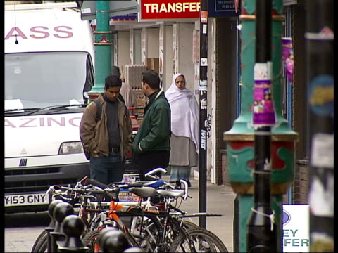 george galloway mp visits brick lane ext back view of asian couple along brick lane woman waering full length hijab/ back view of man wearing turban... - turban stock videos & royalty-free footage