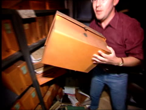 george galloway to sue us publication lib baghdad david blair removing box of files from shelf in iraqi foreign ministry burntout ministry building... - publication stock videos & royalty-free footage
