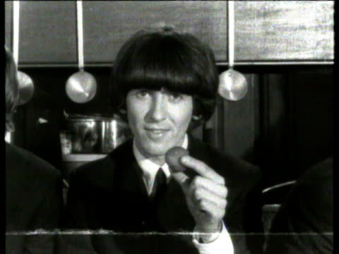 george harrison messing around on 'help' film set all the beatles lined up with props while film director richard lester gives them instructions on... - john lennon stock videos and b-roll footage