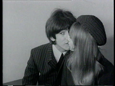 george harrison of the beatles walks through press crowd at press conference with his new wife pattie boyd / the couple perch on a table and kiss for... - 1966 stock-videos und b-roll-filmmaterial