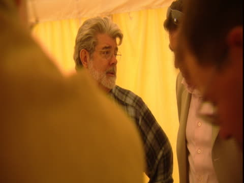 George Lucas carries on a conversation in a crowded room.