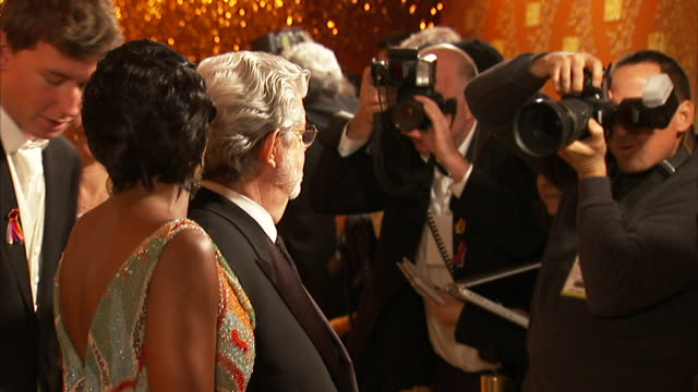 MS George Lucas with Mellody Hobson and son Jett posing for paparazzi as they make their way down the red carpet