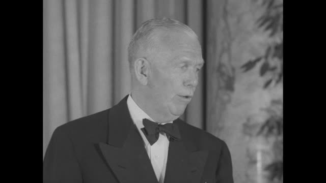 CU George Marshall giving speech / at end of speech Secretary of Defense Frank Pace on Marshall's left and other men sitting at banquet table on...