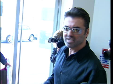 george michael tops radio play list; itn england: london: int side george michael, wearing sunglasses, leaving awards as he stops to answer... - itv london tonight weekend stock-videos und b-roll-filmmaterial