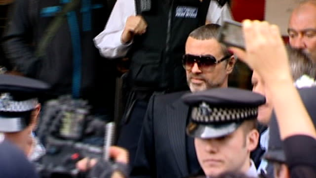 george michael undergoing drug rehabilitation; t24081049 england: london: ext *flash photography* george michael out of court surrounded by police... - itv london tonight weekend stock videos & royalty-free footage