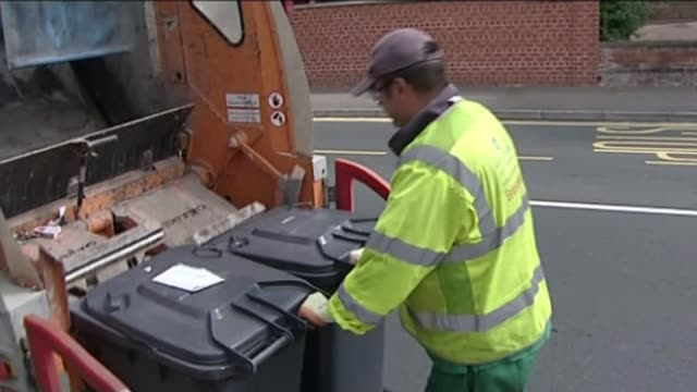 George Osborne delivers Autumn Statement 2015 LIB EXT Council refuse worker emptying wheelie bins into rubbish truck