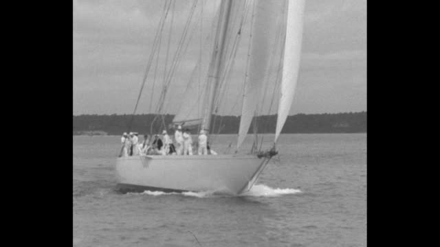 vidéos et rushes de george steers hmy brittania / yacht shamrock gets under way / shot from deck of yacht of water racing by / george on board his yacht pulls rope with... - cowes
