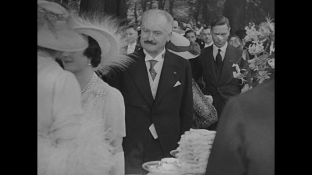 vídeos de stock e filmes b-roll de george vi and queen elizabeth, dressed in formal wear, walk across lawn for garden party in paris / french president albert lebrun with queen at... - formal garden