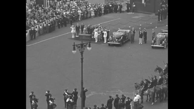 George VI and wife Queen Elizabeth walk down red carpet after leaving building at Battery / they are greeted by various dignitaries woman gives...