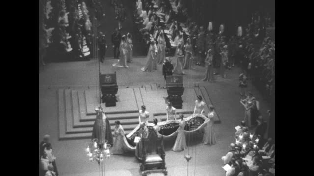 george vi approaches the altar / queen elizabeth walks past thrones / she stands with others / seated george / lr royal family members in royal box... - throne stock videos & royalty-free footage