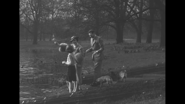 George VI Queen Elizabeth and Princesses Elizabeth and Margaret stroll grounds at Sandringham with dogs / medium CU of Queen with dog / King...