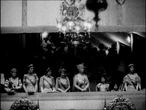george vi walking up aisle with attendants carrying robes at coronation / royalty in balcony at westminster abbey / clergyman placing crown on king... - coronation stock videos and b-roll footage