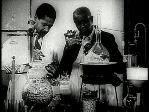 george washington carver with assistant conducting experiments in laboratory / carver examining lab vial - 1944 stock videos and b-roll footage