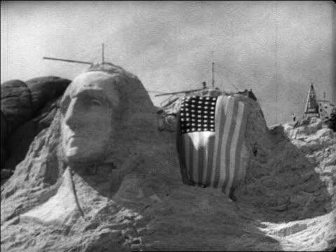 george washington flag covering jefferson at unfinished mt rushmore / newsreel - figura maschile video stock e b–roll
