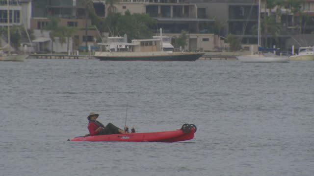 stockvideo's en b-roll-footage met georges river person on pedal kayak passing camera with large homes in background on far shore / locked off shot of big waterfront homes jet ski... - waterfiets