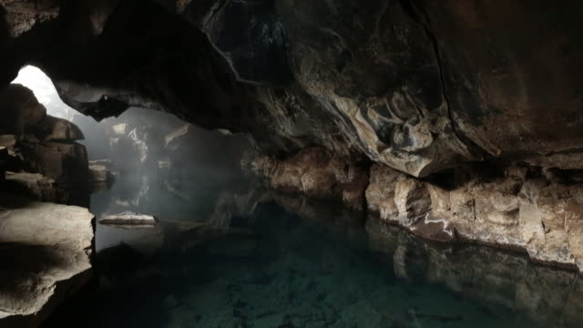 geothermal hot spring flowing in the cave, iceland. - cave stock videos & royalty-free footage