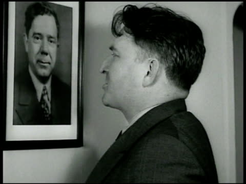 SMITH Gerald LK Smith w/ photo of Huey Long talking to photograph 'one man one gun one bullet' CU Smith signing at Warwick Hotel desk sitting at...