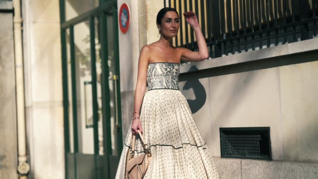 stockvideo's en b-roll-footage met geraldine boublil wears a dior pleated white offshoulder dress with printed features polka dots a dior saddle bag outside dior during paris fashion... - jurk