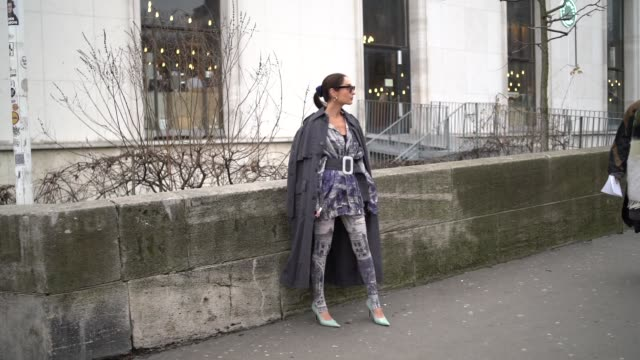 geraldine boublil wears a dress with blue printed drawings, leggings, a dark gray coat, a large belt, outside acne, during paris fashion week -... - legging stock-videos und b-roll-filmmaterial