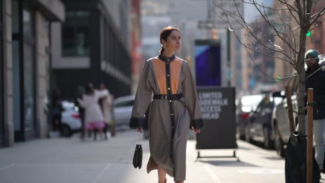 vídeos de stock, filmes e b-roll de geraldine boublil wears a gray and orange coat/dress with buttons and large sleeves a small black bag a belt pointy boots outside brock collection... - casaco curto com mangas
