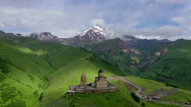 gergeti trinity church at mountain kazbek / georgia - zona erbosa video stock e b–roll
