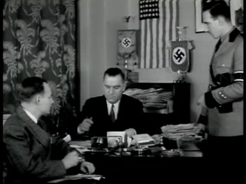vidéos et rushes de german american bund leader fritz kuhn at desk w/ assistants cu flipping pages of list of membership names wwii new york - 1942